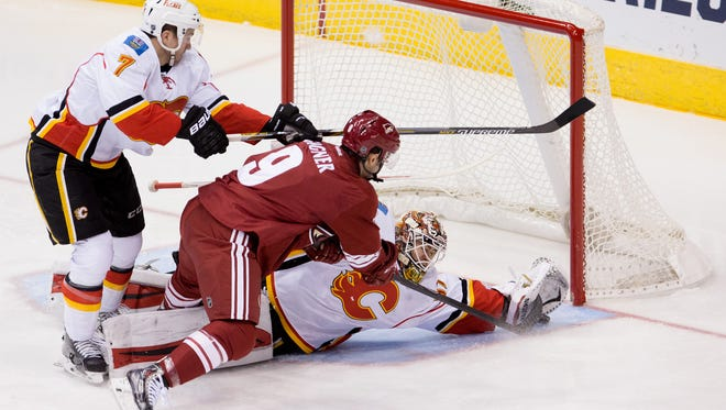 Jan 15, 2015; Glendale; Calgary Flames goalie  Joni Ortio (37) makes a save against Arizona Coyotes center Sam Gagner (9) during the first period at Gila River Arena.