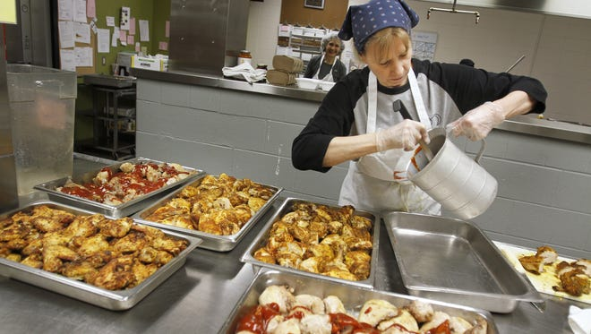 Volunteer Barbara Briggs prepares meals at Second Helpings. The agency accepts donated perishable and overstocked food, then redistributes it, delivering it as meals to more than 80 social-service agencies daily, providing more than 3,500 meals a day.