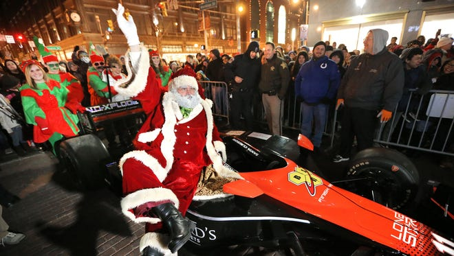 Santa (Ty Stover) struts his stuff before being escorted to the Soldiers and Sailors Monument in an Indy car during Indianapolis' annual Circle of Lights festivities on Nov. 28, 2014.