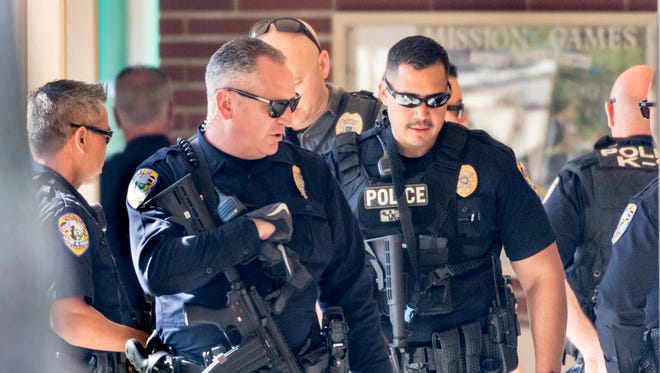 Visalia Police officers leave Visalia Evangelical Free Church after looking for a man with a gun near Giddings and Main Street on Monday, March 12, 2018. Redwood High School was locked down for more than an hour but no person or gun was found in the area.