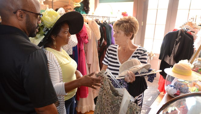 As her husband, Thomas, looks on a left, Felicia Randolph tries on some fashions at Mill Race Village's JM Mead store. Randolph, with the help of shopkeeper Kathy Chester, right, was trying on Victorian garb for the upcoming Northville Heritage Festival that begins on Sept. 16.