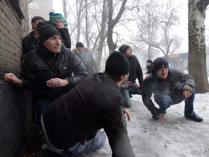 People take cover during shelling in a residential