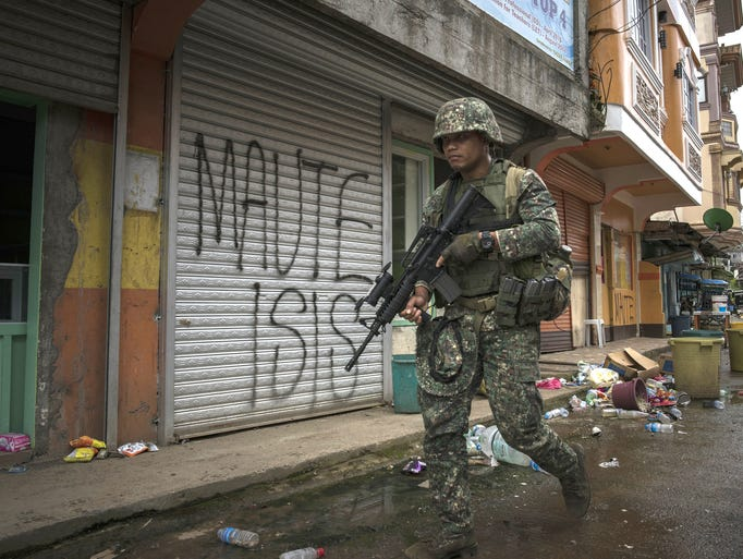A Philippine soldier walks in a cleared street toward
