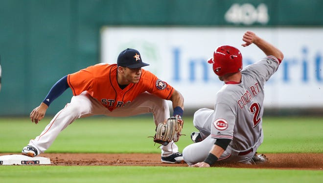 Cincinnati Reds shortstop Zack Cozart (2) is tagged out at second base by Houston Astros shortstop Carlos Correa (1) during the first inning at Minute Maid Park.