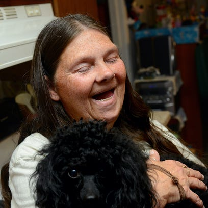 Brenda Leonard, 60,  laughs as she stands in the kitchen