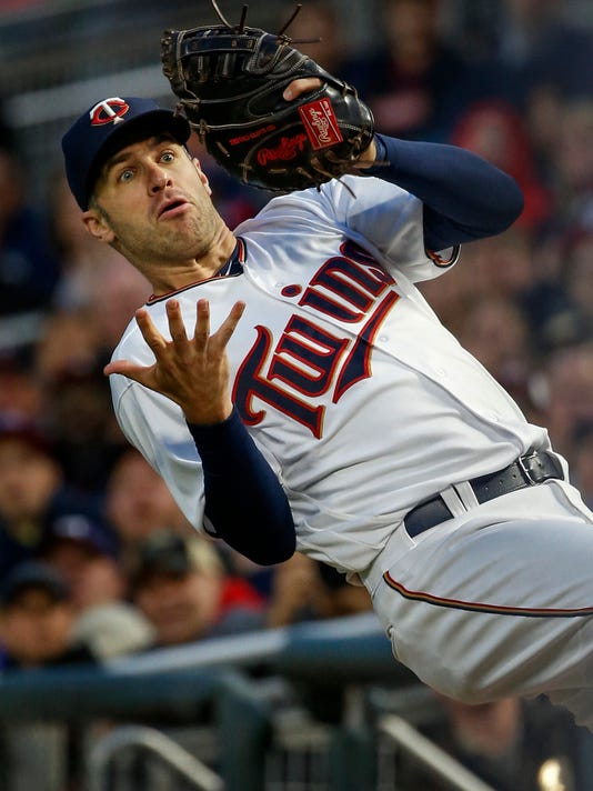 Minnesota Twins first baseman Joe Mauer reacts after almost catching a foul ball by Texas Rangers Robinson Chirinos in the fourth inning of a baseball game Thursday, Aug. 3, 2017, in Minneapolis. (AP Photo/Bruce Kluckhohn)