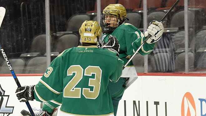 Senior Dominick Posta (facing) and St. Joseph celebrated a Big North Freedom Division title this hockey season, as well as a milestone win for their coach.