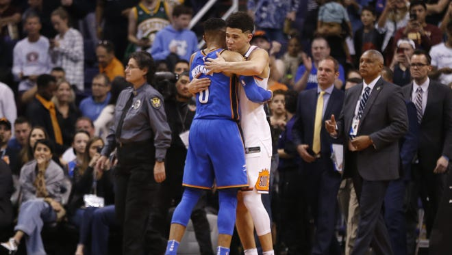 Suns Devin Booker (1) hugs Thunder's Russell Westbrook (0) during the second half at Talking Stick Resort Arena on March 2, 2018 in Phoenix, Ariz.