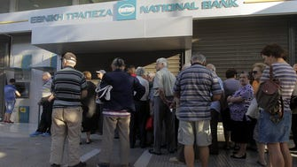 People wait in line outside a National Bank of Greece branch, in Athens on June 29, 2015.