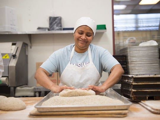 Parvin Akhter, a graduate of Hot Bread Kitchen's Bakers in Training program, rolls loaves at the New York City non-profit.