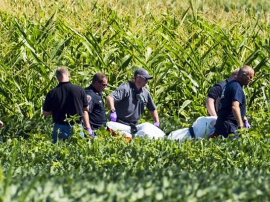 Officials remove the body of a suspect shot by police from a soybean field as members of various Lebanon County law enforcement agencies investigate a police involved shooting in the village of Campbelltown in South Londonderry Township on Monday, August 3, 2015. Police responded to a burglary at the Horseshoe Pike Gun Shop when they encountered the suspect and were fire upon. Police returned fire and the suspect died in a soybean field.  Jeremy Long -- Lebanon Daily News