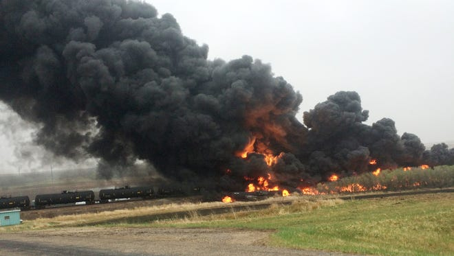 Smoke and fire come from an oil train that derailed Wednesday in Heimdal, North Dakota. Officials say 10 tanker cars on the BNSF caught fire prompting the evacuation of Heimdal where about three dozen people live. No injuries were reported.