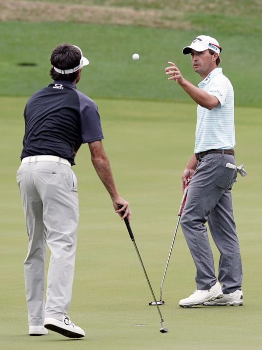 Bubba Watson, left, tosses a ball to opponent Kevin Kisner on the third hole during the final round at the Dell Technologies Match Play golf tournament, Sunday, March 25, 2018, in Austin, Texas. (AP Photo/Eric Gay)