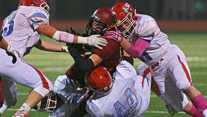 Roosevelt's Austin Johnson (81) is brought down by a group of Lincoln defenders during a game in 2016. High school football participation has dropped from 6,360 players suiting up 30 years ago to 5,500 in 2015.