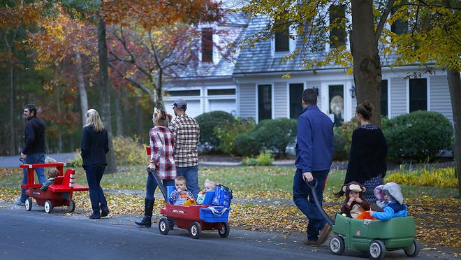 Little tikes get taken through the Woodland Hills neighborhood in Marshfield for Trick or Treating by parents pulling wagons.Greg Derr/ The Patriot Ledger