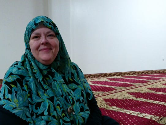 Al-Jallad sitting on the prayer carpet in the women's sanctuary at mosque.