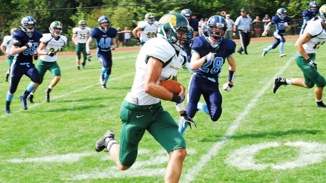 Burr and Burton's Jacob Bayzk (with ball) turns the corner as Mount Mansfield's Johnny Benvenuto (28) pursues during high school football action Saturday at MMU.