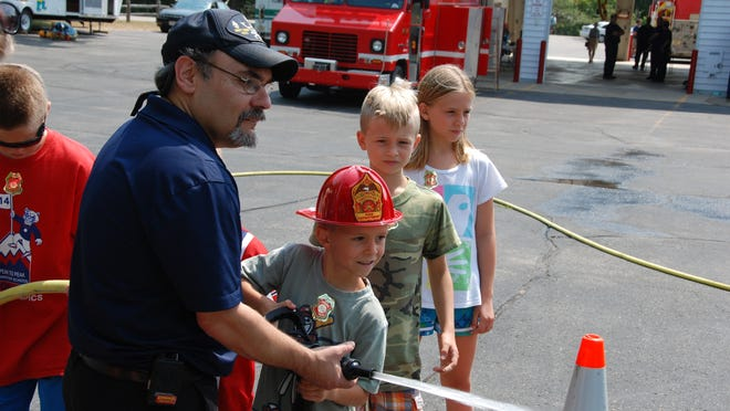 Firefighter Bob Volpe instructs Tegue Healey on how to use a fire hose as brother Kellin and sister Isabelle look on at the Ephraim Fire Department open house.
