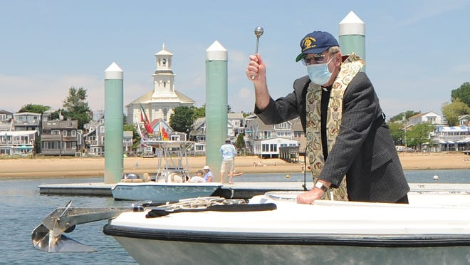 The Rev. Mick McCullough of St. Peter the Apostle Church sprinkles holy water onto a boat during Sunday's Blessing of the Fleet in Provincetown. The event is part of the town's annual Provincetown Portuguese Festival, but was the only event held this year due to the COVID-19 pandemic.