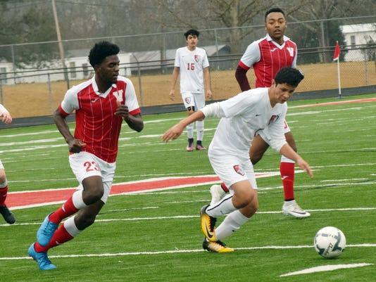 Glenmora High School's Daniel Rubio (7, right) tries to get past Vidalia defenders Saturday during a game held at Tioga High School.