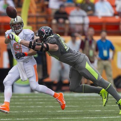 Saints quarterback Drew Brees has a pass broken up by Texans defensive end J.J. Watt at the 2014 NFL Pro Bowl at Aloha Stadium in Honolulu.