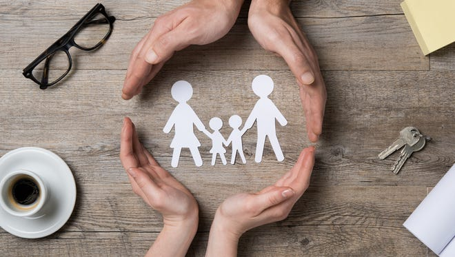 Close up of female and male hands protecting a paper chain family.