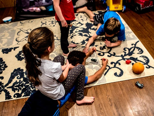 Andrea and Shawn Whitt's adopted children play in the basement of their Newark home.