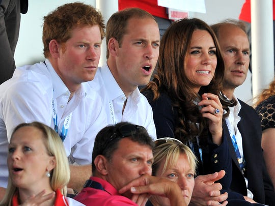 (L-R) Britain's Prince Harry, Prince William, Duke of Cambridge and his wife Catherine, Duchess of Cambridge, react as they watch the women's field hockey match between Wales and Scotland at the Glasgow National Hockey Centre during the 2014 Commonwealth Games in Glasgow, Scotland, on July 28, 2014.