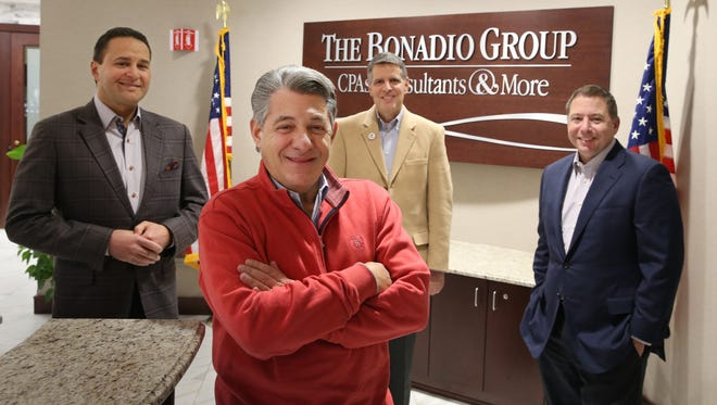 Tom Bonadio, CEO, front center, stands with his managers, from left, Bruce Zicari, practice leader for small business advisory and CEO elect, Mario Urso, Chief of Board of Directors, and Bob Enright, COO, at the Bonadio Group in Pittsford Friday, Feb. 10, 2017.