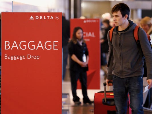 Travelers walk toward the baggage drop area on March 24 for Delta airlines at Seattle-Tacoma International Airport in SeaTac, Wash.
