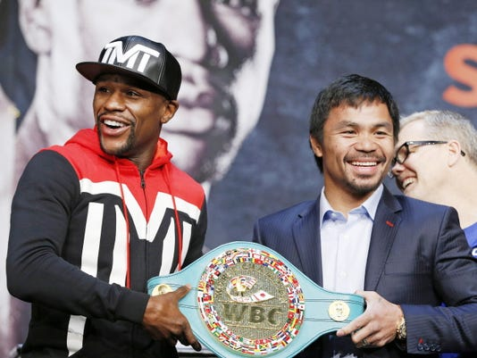 Floyd Mayweather Jr., left, and Manny Pacquiao pose with a WBC belt during a press conference Wednesday, April 29, 2015, in Las Vegas. Mayweather will face Pacquiao in a welterweight boxing match in Las Vegas on May 2. (AP Photo/John Locher)