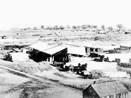 "The O.T. Bassett lumberyard in 1881. The Pioneer Association of El Paso mentions it in Maurice Edwards' biography: ""A photograph of the lumberyard ... gives a vivid idea of the insignificance of the town at that time, only a few adobe houses besides the lumberyard being visible, for the picture not only gives the enterprise but also the entire town."""
