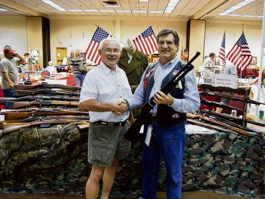 Vic Currier, right, president of the Lincoln-Otero Pfc Robert G. Montoya Chapter of the Vietnam Veterans of America, congratulates raffle ticket holder Rickie Prichard of Ruidoso, at a previous gun show.