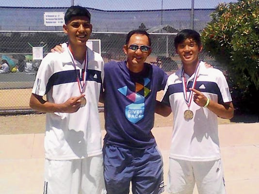 Courtesy Photo   Elias Vigil, left, Deming Coach Chester Kwong and Ezekiel Kwong, celebrate a photo op. following the District 3-6A doubles championship last Saturday in Las Cruces.