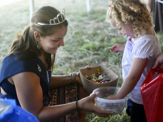 Franklin County Fair Queen Kayla Hartung, left, gives candy to Emma Baker, 2, of Chambersburg on Saturday during Franklin Fall Farm Fun Festival at the Cornerstone Dairy Farm in Greene Township.
