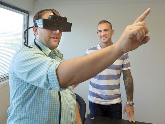 Chris Coulson, left, tries on Meta augemented reality glass with partner Anthony Billet at Fuse York, a collaborative in-sourcing space Thursday, Oct. 8, 2015. The two are partnering to develop virtual and augmented reality applications. Billet's company abSketches and Coulson Technologies are looking for like-minded tenants in the former Springettsbury Township post office. Bill Kalina - bkalina@yorkdispatch.com