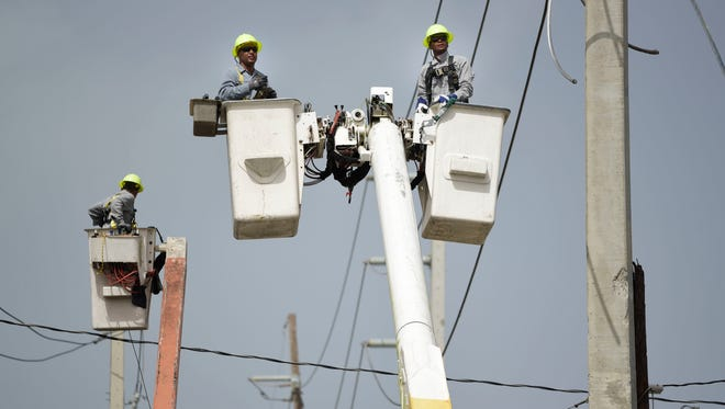 A brigade from the Electric Power Authority repairs distribution lines damaged by Hurricane Maria in the Cantera community of San Juan, Puerto Rico, on Oct. 19, 2017.