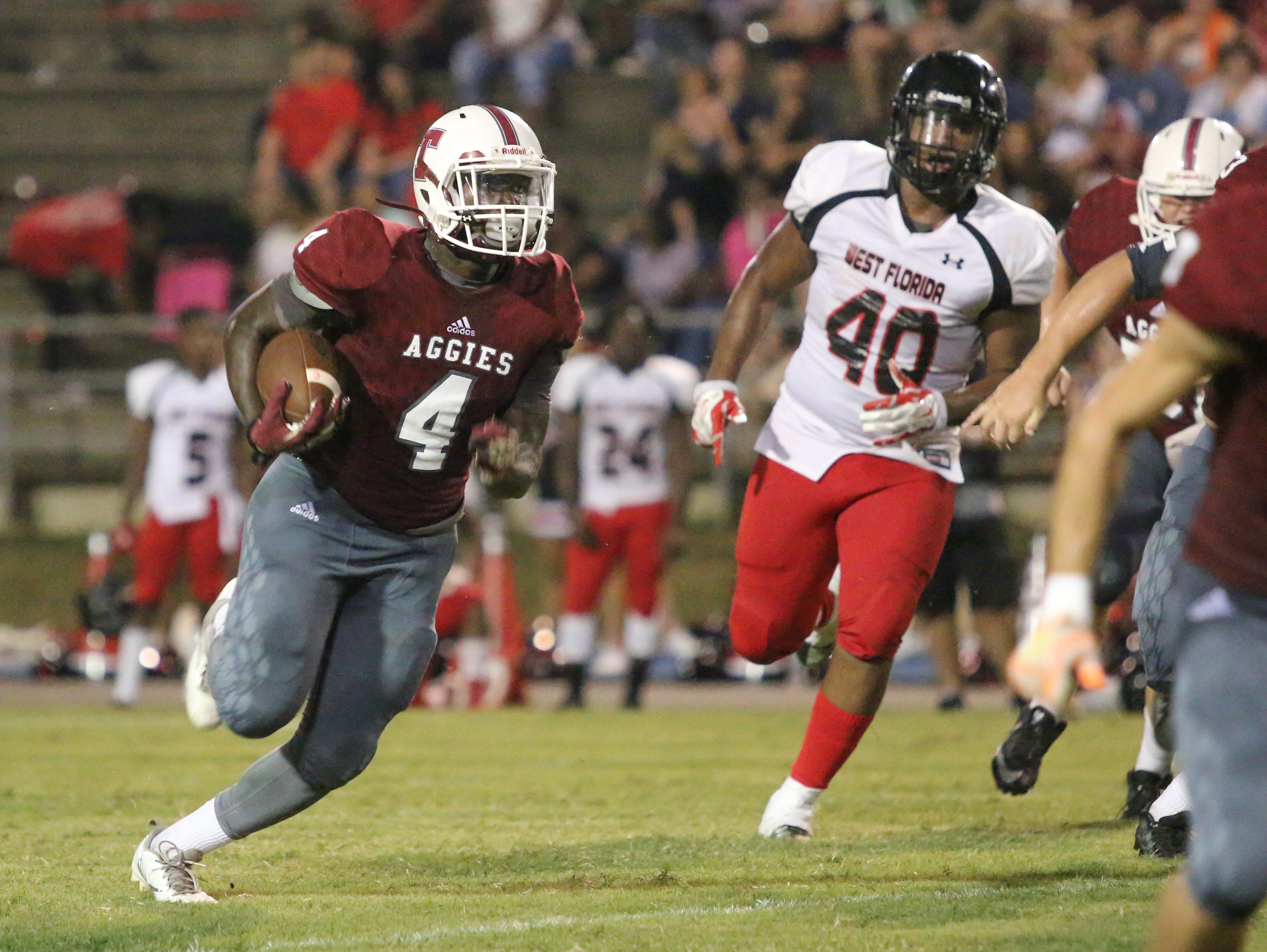 Tate's Ladarryl Paige (4) races past the line of scrimmage Friday night at Tate High School.