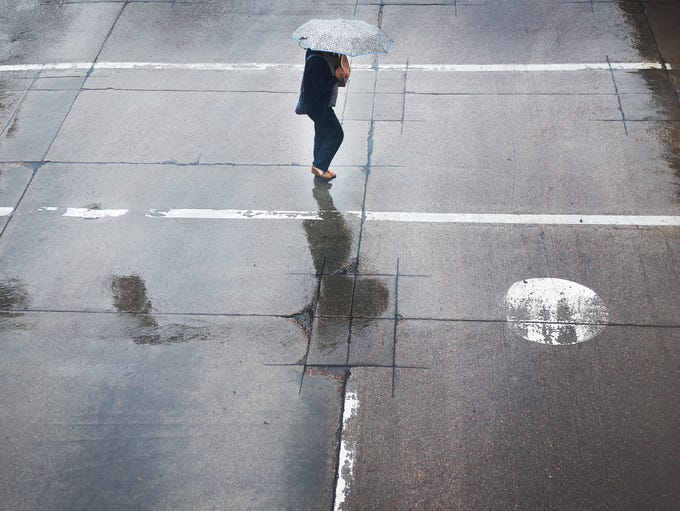 A Pedestrian crosses the street downtown Wednesday,