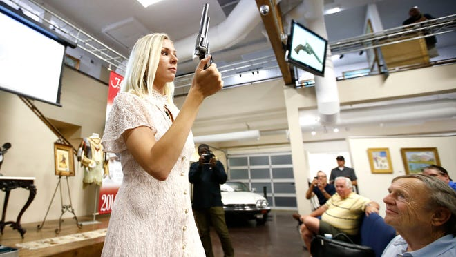 Kayla Wilbur, auction assistant at J. Levine Auction & Appraisal in Scottsdale, Ariz., displays Wyatt Earp's Colt .45-caliber revolver used at the O.K. Corral gunfight. A New Mexico telephone bidder won the firearm for $225,000 on April 17, 2014.