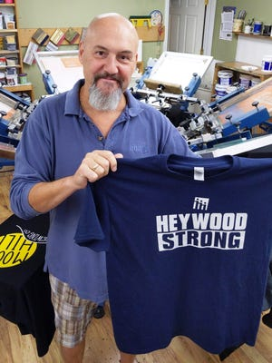 """Brian LaRoche, owner of Sharp Image Inc. in Gardner, displays a """"Heywood Strong"""" shirt, which he designed to help raise money to support local health care workers."""