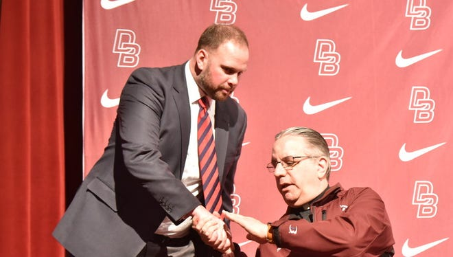 New Don Bosco head football coach Mike Teel accepts congratulations from school Director/President Fr. James Heuser.