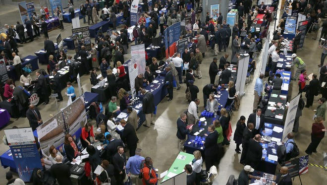 People visit booths of prospective employers during the Hiring Our Heroes job fair at the Washington Convention Center on Jan. 10 in Washington, D.C.  More than 80 companies participated in the fair, hosted by the U.S. Chamber of Commerce for U.S. veterans and military spouses.