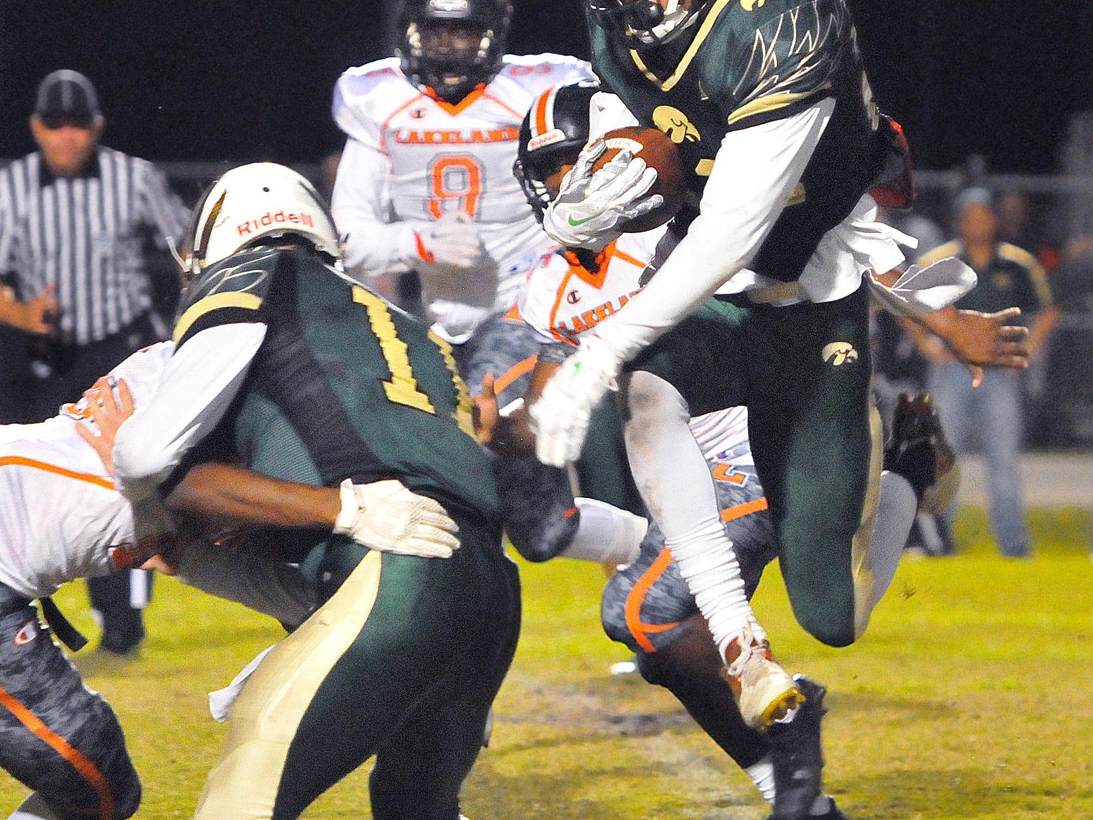Viera High's#23 Alex Cabrera hurdles Lakeland High defenders on his way for a Viera High touchdown during Friday nights regional finals held at Viera High School stadium.
