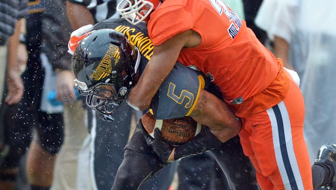 Southern Miss wide receiver D.J. Thompson is brought down by a UTEP player after catching a long pass during a rainy game against UTEP at M.M. Roberts Stadium Saturday, Oct. 31.