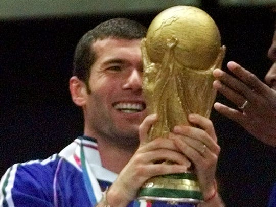Zinedine Zidane of France displays the World Cup after the final of the soccer World Cup 98 between Brazil and France at the Stade de France in Saint Denis, north of Paris, Sunday, July 12, 1998. France beat Brazil with a 3-0 score.