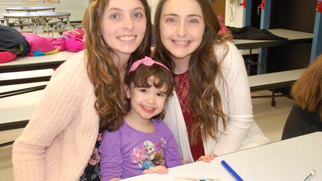 Eighth grade students Gabriella Poth and Skyler Rafferty, with their preschool Prayer Partner Samantha Innella, make cards to attach to corn bread.