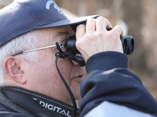 Bruce Riede of Ridgefield was one of about 50 people who looked through, binoculars, scopes or cameras to try to catch a glimpse of eagles on the other side of Overpeck Creek on Sunday, Jan. 21, 2018.