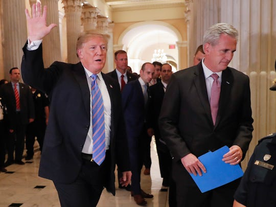 President Donald Trump, left, gestures as he walks with House Majority Leader Kevin McCarthy of Calif., right, while leaving the U.S. Capitol in Washington after meeting with GOP leadership, Tuesday, June 19, 2018. Walking behind them is Stephen Miller, center, White House senior adviser.