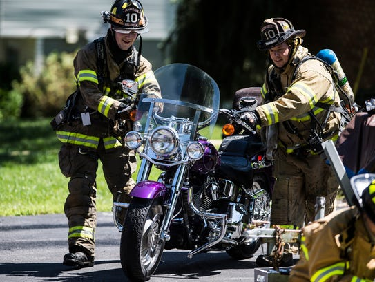 Firefighters remove a motorcycle from the garage at